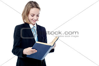 Small school girl reading a book