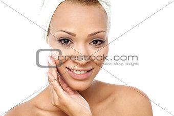 Beautiful woman applying moisturizer