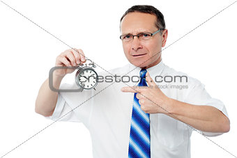 Smiling businessman holding an alarm clock