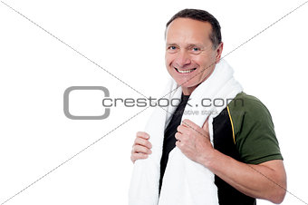 Aged male trainer posing after his workout