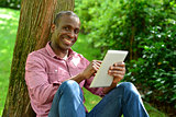 Handsome man with tablet in the park