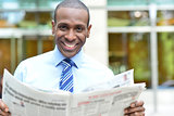 Smiling executive holding newspaper