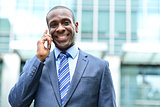 Smiling male professional talking on cell phone