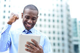 Businessman celebrates his success with tablet