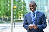 Smiling businessman holding smartphone