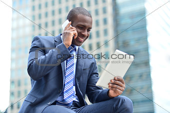 African executive with tablet pc and cellphone
