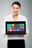 Smiling beautiful woman holding laptop