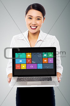 Smiling beautiful woman holding laptop