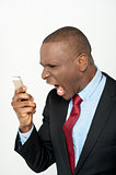 Angry business man screaming on cell phone