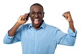 Excited african man talking on mobile phone