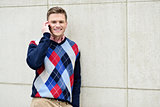 Happy man leaning against wall with cell phone