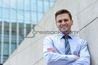 Smiling businessman standing against wall