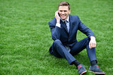 Corporate male relaxing on grass meadow