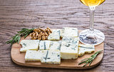 Roquefort with glass of white wine on the wooden board