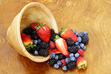 berry assortment - raspberries, blackberries, strawberries, blueberry on a wooden background