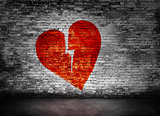 Shape of broken heart on brick wall