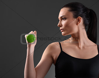 Fitness woman working out with green dumbbell