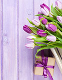 Purple tulips and gift box over wooden table