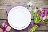 Purple tulip bouquet and plate on wooden table