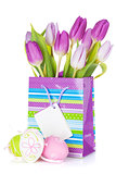 Purple tulip bouquet in gift bag and easter eggs