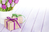 Purple tulip bouquet and gift box on wooden table