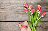 Colorful tulips and gift box on wooden table