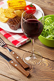 Glass of red wine, steak with grilled potato, corn and salad