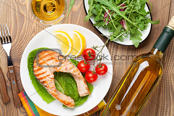 Grilled salmon and whtie wine on wooden table