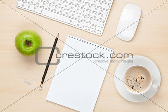Office table with notepad, computer and coffee cup
