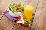 Healthy salad, orange glass and tape measure