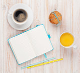 Cup of orange juice, coffee cup, gingerbread cookies and notepad