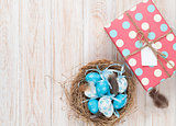 Easter with blue and white eggs in nest and gift box