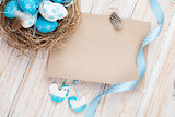 Easter greeting card with blue and white eggs in nest and decor