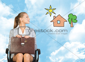 Business woman in skirt, blouse and jacket, sitting on chair imagines house with tree. Against background of blue sky, clouds