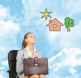Business woman in skirt, blouse and jacket, sitting on chair, holding briefcase imagines house with tree. Against background of blue sky, clouds