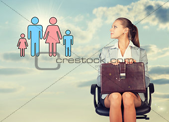 Business woman in skirt, blouse and jacket, sitting on chair, holding briefcase imagines family. Against background of sky, clouds