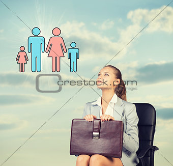 Business woman in skirt, blouse and jacket, sitting on chair imagines family. Against background of sky, clouds