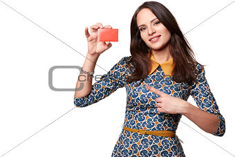 Beautiful woman in colorfull dress holding empty credit card and pointing at it,  isolated on white background
