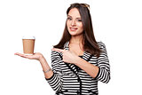 Happy Woman in Stripe Jacket Points Out to the Cup of Coffee. Isolated