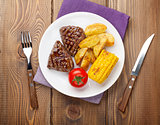 Steak with grilled potato, corn and salad on wooden table
