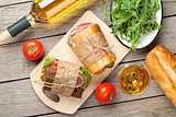 Sandwiches and white wine on wooden table