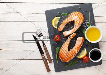 Grilled salmon, salad and condiments on wooden table