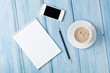 Coffee cup, smartphone and blank notepad on wooden table backgro