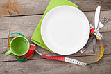 Plate with measure tape, cup, knife and fork. Diet food on woode