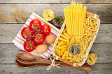 Various pasta, tomatoes and kitchen utensils