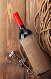 Red wine bottle and corkscrew on wooden table