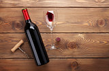 Red wine bottle, glass of wine and corkscrew