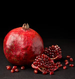 pomegranate with pieces on dark background