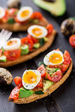 Bruschetta with tomato, avocado and quail egg