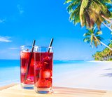 two glasses of red cocktail with blur beach and palm